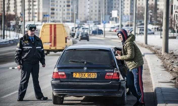Полицейский и мужчина возле машины