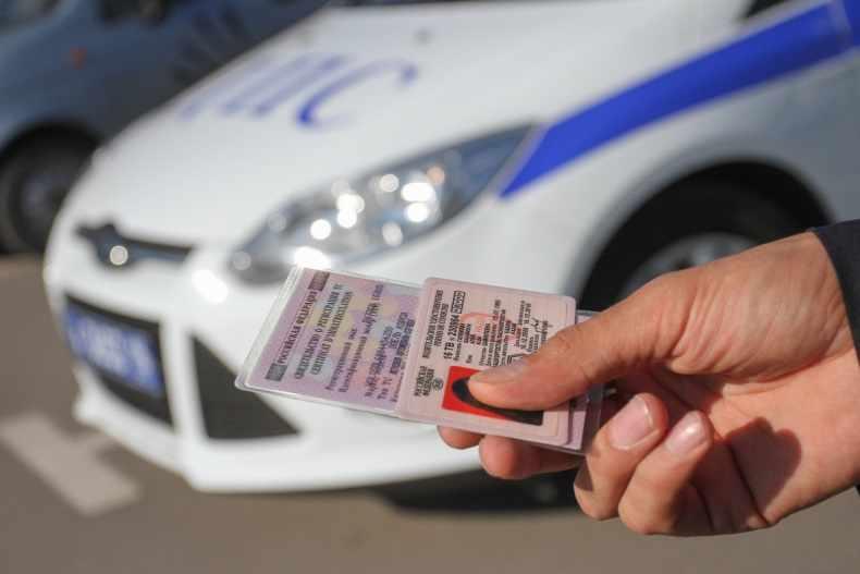 Водительские права на фоне машины ДПС