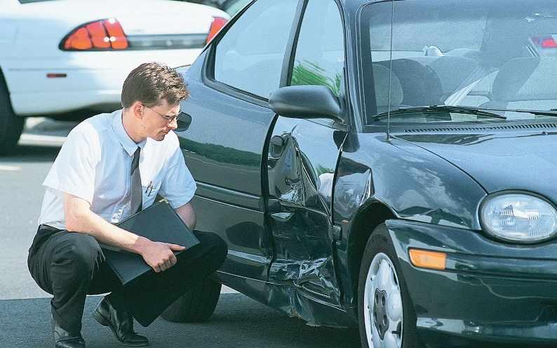 Мужчина сидит у разбитой машины