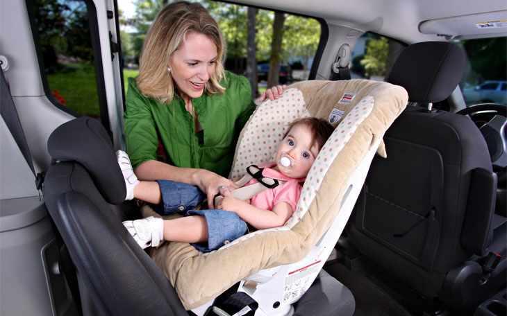 Мама сажает ребенка в детское кресло
